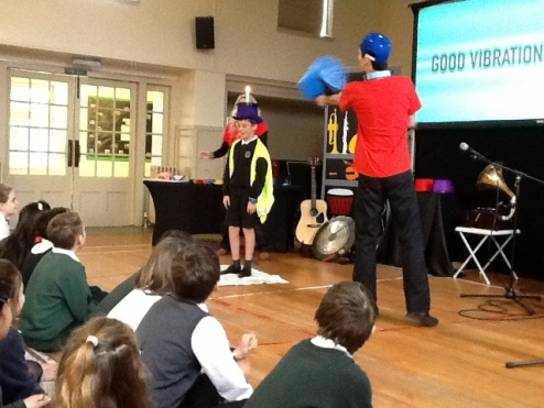 Pupil on stage demonstrating how sounds can be made from different objects
