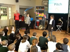 Pupils on stage demonstrating how sounds can be made from different objects