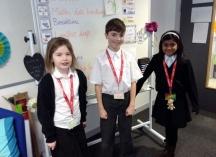 Three pupils proudly displaying their reading riot lanyards