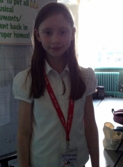 A pupil proudly displaying her reading riot lanyard