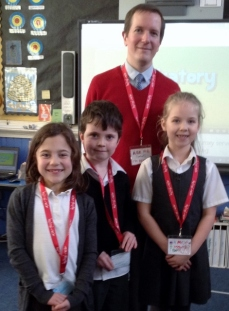Mr Harrison and 3 pupils proudly displaying their reading riot lanyards