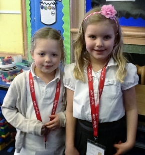 Two pupils proudly displaying their reading riot lanyards