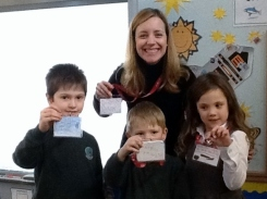 Mrs Norman and 3 pupils proudly displaying their reading riot lanyards