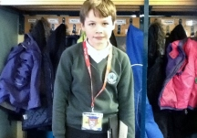 A pupil proudly displaying his reading riot lanyard