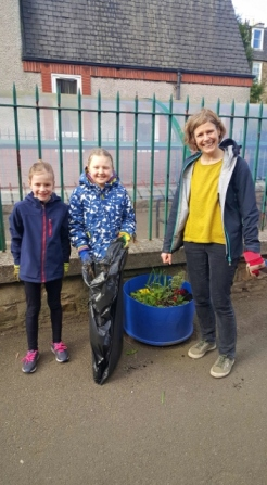 Two pupils and a parent helping to weed the planters around the school