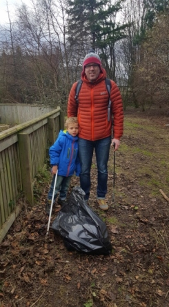 A pupil and parent picking up litter in the forest area of the school grounds.