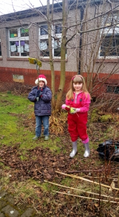 Two pupils picking litter in the central garden.