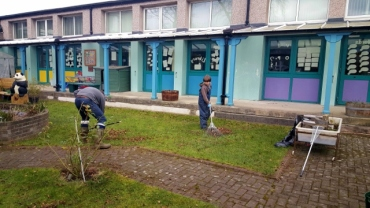 A pupil and parent volunteer raking leaves in the central garden.