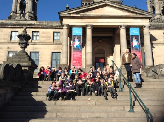 P2C pupils sitting on steps outside Art Gallery's entrance showing the sculptures that they've made.