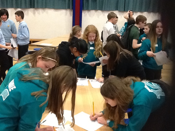 Pupils writing down the answers to their questions