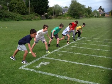 Male pupils getting ready to sprint