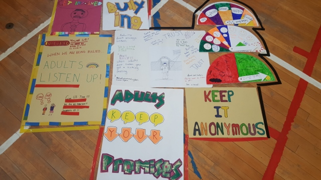 "Posters from another school. One poster reads ""Adults listen up!"""