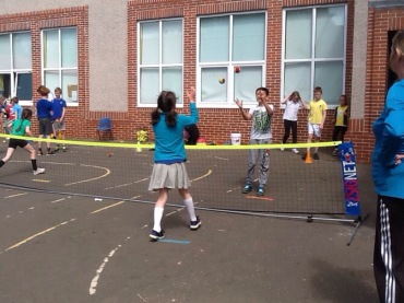 Pupils practising catching a tennis ball for the game of jail.